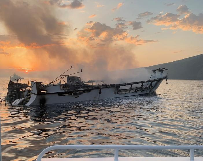 "The dive boat Conception smolders Sept. 2, 2019, in the waters off Santa Cruz Island. <span class=""copyright"">(Ventura County Fire Department)</span>"