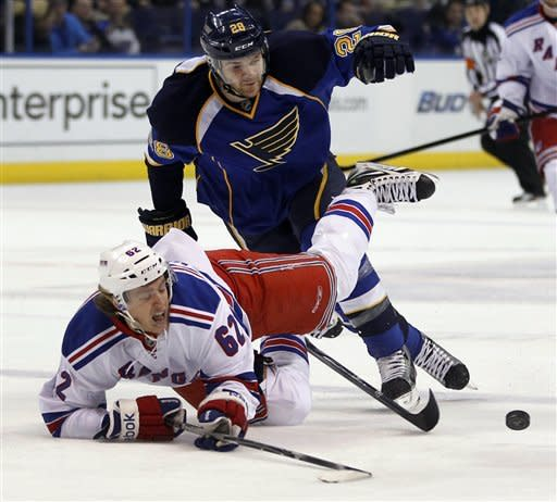 New York Rangers' Carl Hagelin, of Sweden, falls after colliding with St. Louis Blues' Carlo Colaiacovo, top, during the first period of an NHL hockey game Thursday, Dec. 15, 2011, in St. Louis. (AP Photo/Jeff Roberson)