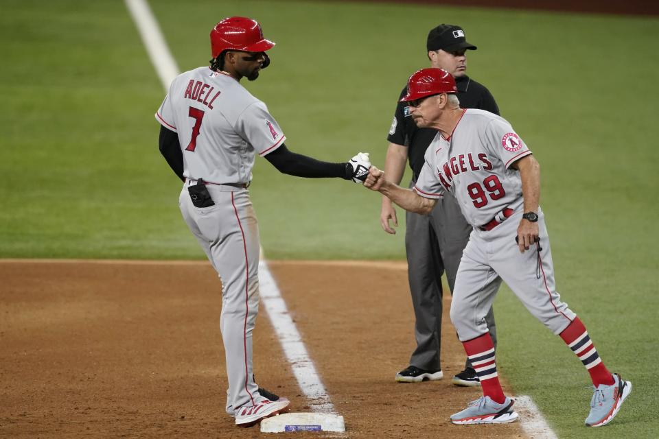 Los Angeles Angels' Jo Adell, left, celebrates his run-scoring single with first base coach Bruce Hines (99) in the seventh inning of a baseball game against the Texas Rangers as umpire Nick Mahrley stands by the bag in Arlington, Texas, Tuesday, Aug. 3, 2021. (AP Photo/Tony Gutierrez)
