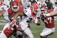 Georgia running back Nick Chubb (27) pushes past Arkansas defenders linebacker Martrell Spaight (47), safety Rohan Gaines, bottom left, and defensive end JaMichael Winston, top left, in the first quarter of an NCAA college football game in Little Rock, Ark., Saturday, Oct. 18, 2014. (AP Photo/Danny Johnston)