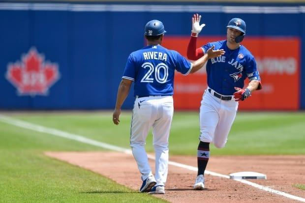 Toronto Blue Jays' Randal Grichuk, right, is congratulated after hitting a solo home run against the Tampa Bay Rays in Buffalo, N.Y. The Blue Jays could be back in Toronto by the end of July, pending the outcome of an application to the federal government. (Adrian Kraus/The Associated Press - image credit)