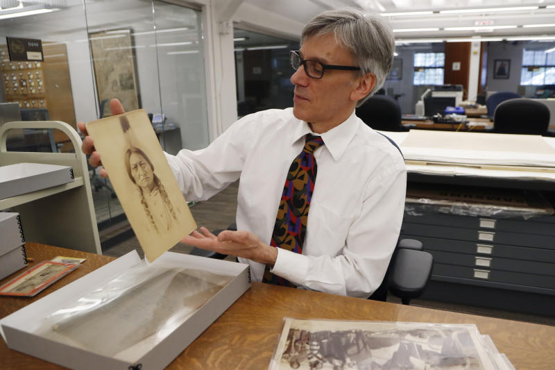 In this Thursday, Nov. 14, 2019 photo, University of Michigan William Clements Library Curator of Graphics, Clayton Lewis, shows a photograph of Sitting Bull from the photographic collection acquired by the library in 2016 from Richard Pohrt Jr. in Ann Arbor, Mich. The trove, representing some 80 indigenous groups, includes photos from government-sponsored expeditions, stereographic and cartes de visites. (AP Photo/Carlos Osorio)