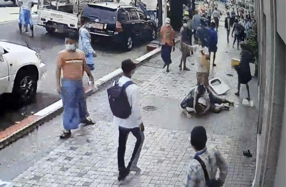 In this image taken from video obtained by Than Lwin Khet News, a woman helps an unidentified man lying on the sidewalk of Sule Pagoda Road after he was attacked by a group of men in Yangon, Myanmar, Thursday, Feb. 25, 2021. Members of a group supporting Myanmar's military junta have attacked and injured people protesting against the army's Feb. 1 seizure of power that ousted the elected government of Aung San Suu Kyi. (Than Lwin Thet News via AP)