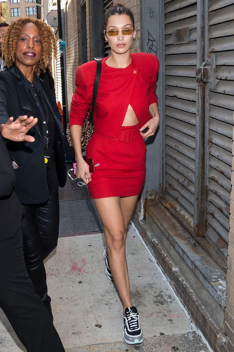 <p>In a red skirt suit, Nike Air Zoom sneakers, leopard print bag, and rectangular sunglasses while out in NYC.</p>