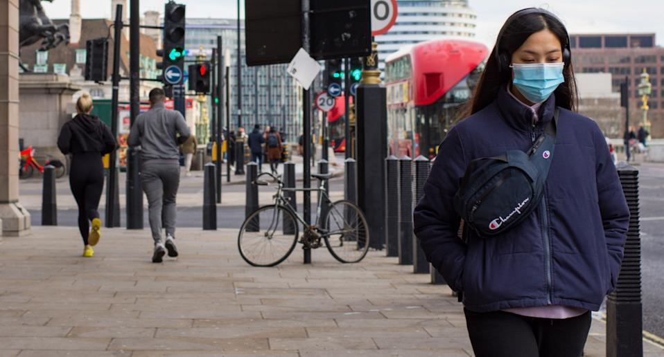 Woman wears a face mask as she walks through London. Source: Getty Images