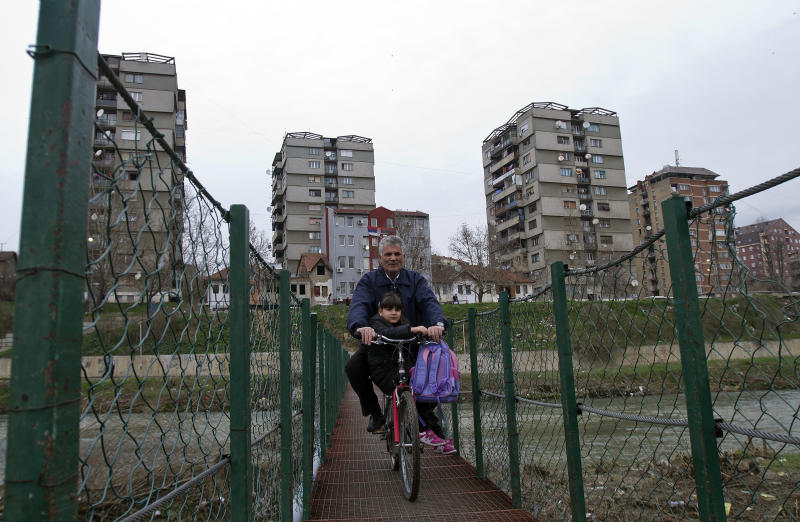 A Kosovo Albanian man rides his bicycle across a makeshift bridge that separates the ethnically divided northern Kosovo town of Mitrovica, Tuesday, April 2, 2013. The leaders of Serbia and Kosovo are negotiating Tuesday on one of the most important issues dividing them, as Serbia strains to meet conditions for eventual membership in the European Union. (AP Photo/Visar Kryeziu)