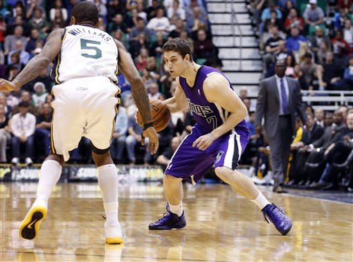 Sacramento Kings guard Jimmer Fredette (7) is defended by Utah Jazz guard Mo Williams (5) during the first half of their NBA basketball game in Salt Lake City, Friday, Nov. 23, 2012. (AP Photo/Jim Urquhart)