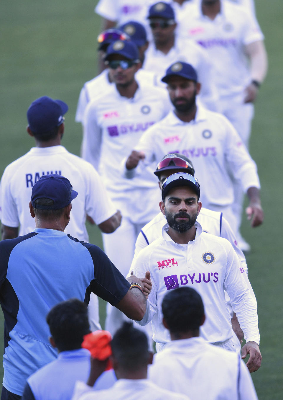 India's Virat Kohli, center right, shakes hands with coach Ravi Shastri following their loss to Australia on the third day of their cricket test match at the Adelaide Oval in Adelaide, Australia, Saturday, Dec. 19, 2020. (AP Photo/David Mariuz)