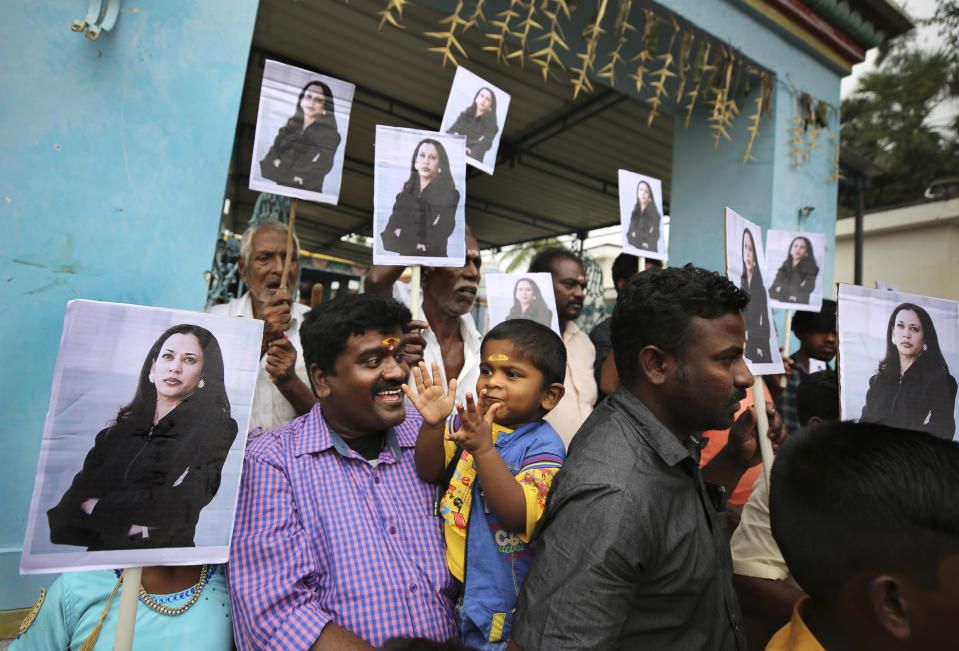 FILE - In this Jan. 20, 2021, file photo, a child reacts as villagers hold placards featuring Vice President Kamala Harris after participating in special prayers ahead of the inauguration, outside a Hindu temple in Thulasendrapuram, the hometown of Harris' maternal grandfather, south of Chennai, Tamil Nadu state, India. (AP Photo/Aijaz Rahi, File)