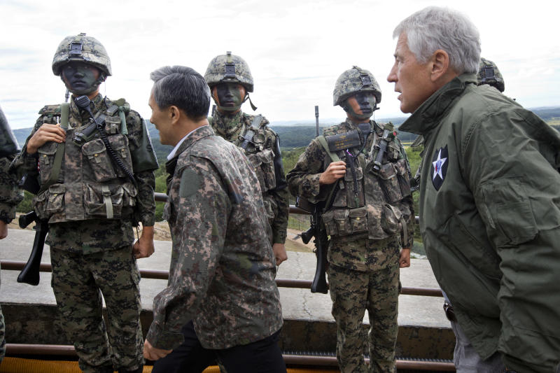 U.S. Secretary of Defense Chuck Hagel, right, walks past South Korean soldiers with South Korean Defense Minister Kim Kwan-jin, left, during a tour of the Demilitarized Zone (DMZ), the military border separating the two Koreas, in Panmunjom, South Korea, on Monday, Sept. 30, 2013. Hagel is in Sourth Korea for celebrations marking the 60th anniversary of the ending of the Korean War before heading to Japan for ministerial meetings. (AP Photo/Jacquelyn Martin, Pool)
