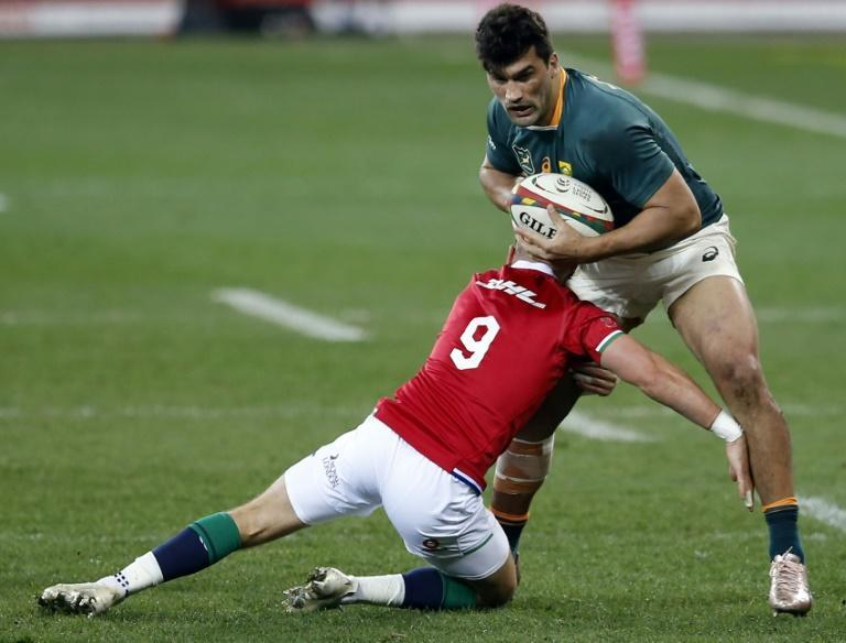 South Africa centre Damian de Allende (R) is tackled by British and Irish Lions scrum-half Ali Price (L) in Cape Town