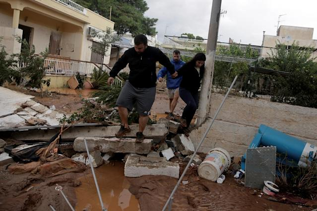 <p>Locals walk among debris in a yard, following a heavy rainfall in the town of Mandra, Greece, Nov. 15, 2017. (Photo: Alkis Konstantinidis/Reuters) </p>