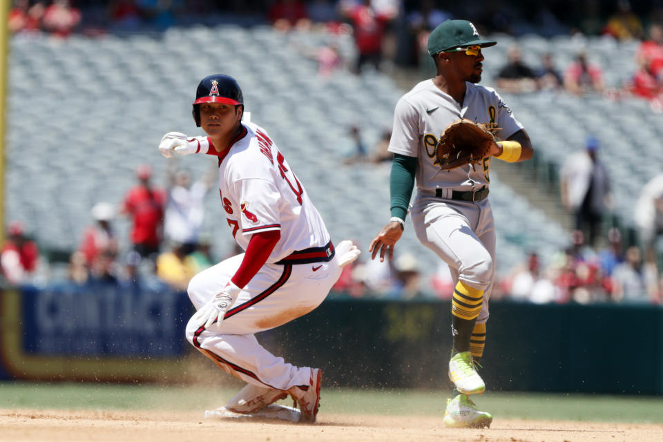Los Angeles Angels designated hitter Shohei Ohtani, left, slides into second with an RBI-double as Oakland Athletics second baseman Tony Kemp, right, gets out the way during the third inning of a baseball game in Anaheim, Calif., Saturday, July 31, 2021. (AP Photo/Alex Gallardo)