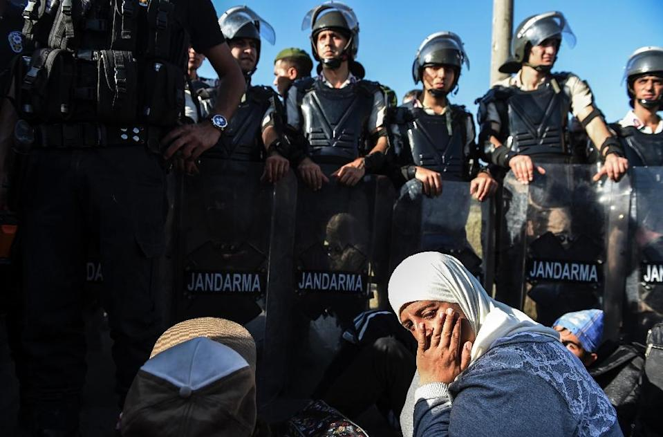 Syian refugees sit in front of a police barricade as they march along the highway towards the Turkish-Greek border at Edirne on September 18, 2015 (AFP Photo/Bulent Kilic)