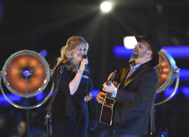 """CORRECTS YEAR TO 2019 - Trisha Yearwood, left, and Garth Brooks perform """"Old Flames Can't Hold a Candle To You"""" at MusiCares Person of the Year honoring Dolly Parton on Friday, Feb. 8, 2019, at the Los Angeles Convention Center. (Photo by Chris Pizzello/Invision/AP)"""