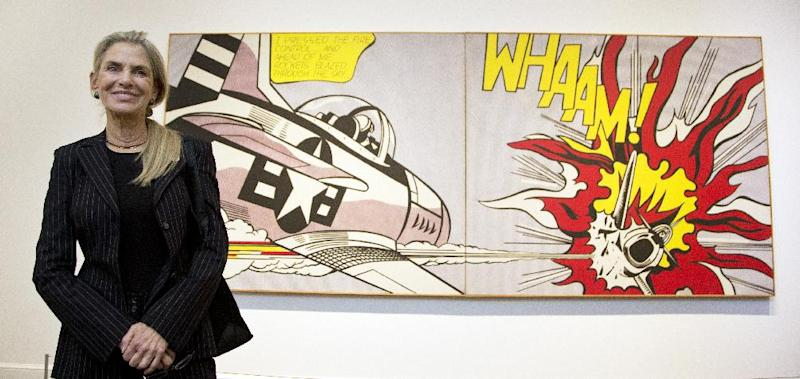 FILE - In this Oct. 9, 2012 file photo, Dorothy Lichtenstein, widow of artist Roy Lichtenstein, poses beside her husband's artwork, a 1963 oil and magna on canvas entitled; Whaam! during the press preview of his first major exhibition since his death, at the National Gallery of Art in Washington. (AP Photo/Manuel Balce Ceneta, File)