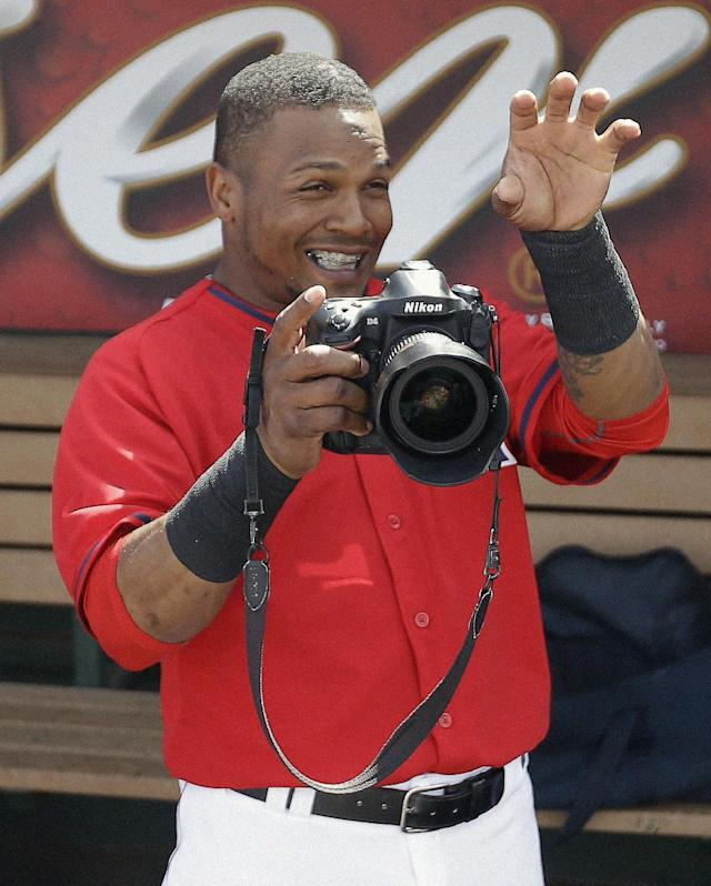 Los Angeles Angels's Erick Aybar has fun with a camera before an exhibition spring training baseball game against the Chicago White Sox, Thursday, March 13, 2014, in Tempe, Ariz. (AP Photo/Morry Gash)