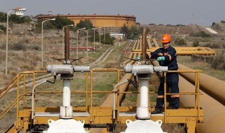 A worker checks the valve gears of pipes linked to oil tanks at Turkey's Mediterranean port of Ceyhan