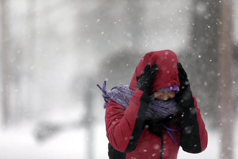 Srirupa Chatterjee holds her hood as she crosses a street Sunday, Jan. 5, 2014, in St. Louis. Heavy snow continues to fall Sunday with forecasters calling for up to a foot (30 centimeters) in eastern Missouri and parts of central Illinois followed by bitter cold. (AP Photo/Jeff Roberson)