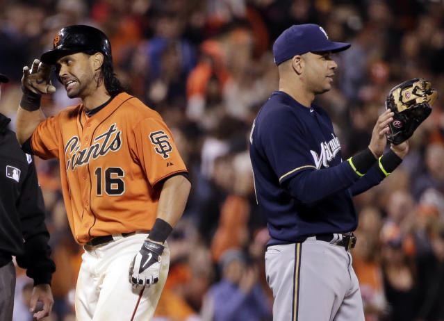 San Francisco Giants' Angel Pagan salutes toward his dugout after a stand-up triple, next to Milwaukee Brewers third baseman Aramis Ramirez during the fifth inning of a baseball game Friday, Aug. 29, 2014, in San Francisco. (AP Photo/Marcio Jose Sanchez)