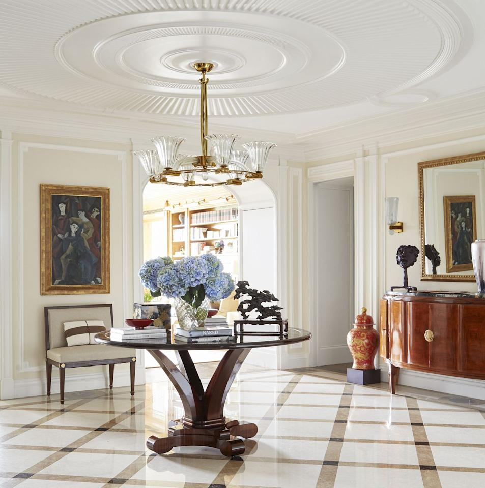 """<p>This timelessly decorated foyer by <a href=""""https://cullmankravis.com"""" target=""""_blank"""">Cullman & Kravis</a> makes a visual impact thanks to an oversized ceiling medallion and diamond-patterned marble floor. A French Art Deco console from <a href=""""https://kitkemp.com"""" target=""""_blank"""">Kit Kemp Antiques</a>, a table from <a href=""""https://craigvandenbrulle.com"""" target=""""_blank"""">Craig Van Den Brulle</a>, and a custom settee from <a href=""""https://www.anthonylawrence.com"""" target=""""_blank"""">Anthony Lawrence-Belfair</a> warm the space.</p>"""