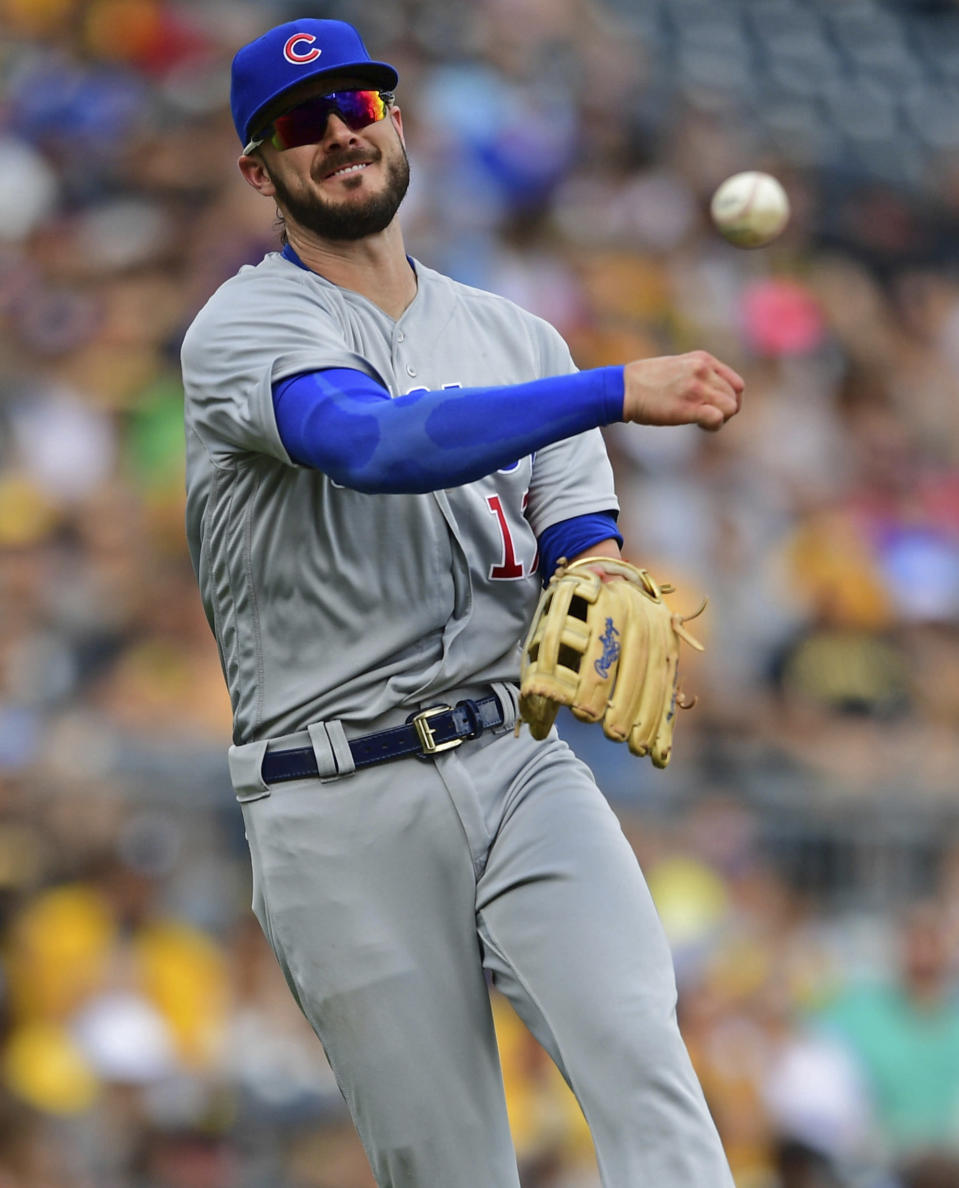 Chicago Cubs' Kris Bryant throws throws to first base to try to get out Pittsburgh Pirates' Erik Gonzalez in the fifth inning of a baseball game, Saturday, Aug. 17, 2019, in Pittsburgh. Gonzalez advanced to second base on a throwing error by Bryant. (AP Photo/David Dermer)