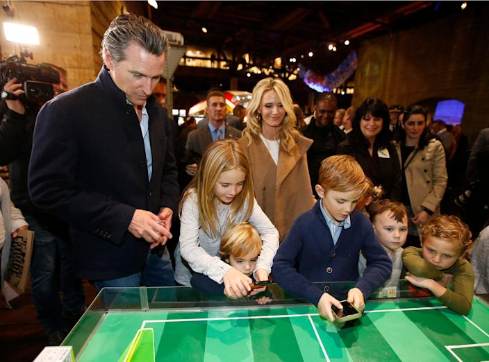 In this Jan. 6, 2019, file photo Gov. Gavin Newsom, left, and his wife, Jennifer Siebel Newsom, center, watch their children, daughter Montana, second from left, and sons, Dutch, foreground, and Hunter, foreground fourth from left, operate robot games at the California Railroad Museum, Sacramento, Calif. Newsom said this weekend that his family is under quarantine after a recent exposure to COVID-19. The governor's family tested negative for the virus on Nov. 22, 2020.