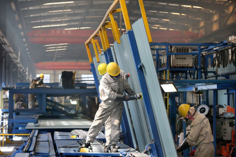 People work inside a factory of a shipbuilding industrial park at a port in Qidong city of Nantong