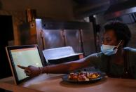 """An employee using the """"Funky Pay"""" app informs clients that their order is ready, at Funky Pizza restaurant, where the app replaces waiters, in Palafrugell"""