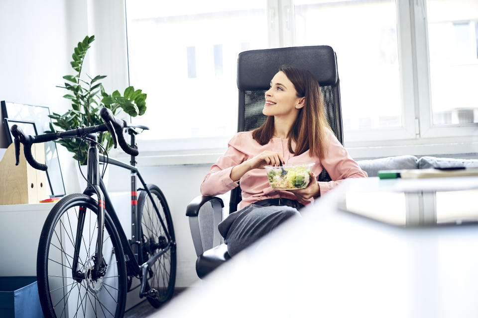 Businesswoman having lunch break in office sitting at desk. Image: Getty Images