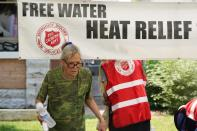 A pedestrian takes a bottle of water at a Salvation Army hydration station during a heatwave as temperatures hit 115-degrees, Tuesday, June 15, 2021, in Phoenix. (AP Photo/Ross D. Franklin)