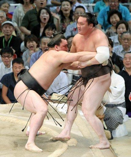 "Mongolian-born champion, or ""ozeki"", Harumafuji (left) pushes his compatriot and grand champion, or ""yokozuna"", Hakuho (right), out of the ring to take the title at the Nagoya Grand Sumo tournament in July. 2012"