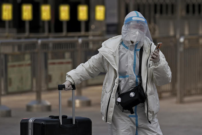 A woman wearing a protective gear to help curb the spread of the coronavirus walks with her luggage arrives to the railway station to catch her train in Beijing, Wednesday, Jan. 27, 2021. China has given more than 22 million COVID vaccine shots to date as it carries out a drive ahead of next month's Lunar New Year holiday, health authorities said Wednesday. (AP Photo/Andy Wong)