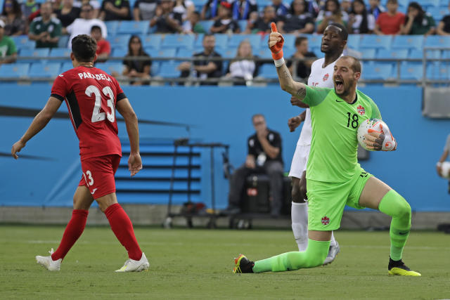 Canada's Milan Borjan (18) reacts after a save against Cuba's Luis Paradela (23) during the first half of a CONCACAF Golf Cup soccer match in Charlotte, N.C., Sunday, June 23, 2019. (AP Photo/Chuck Burton)