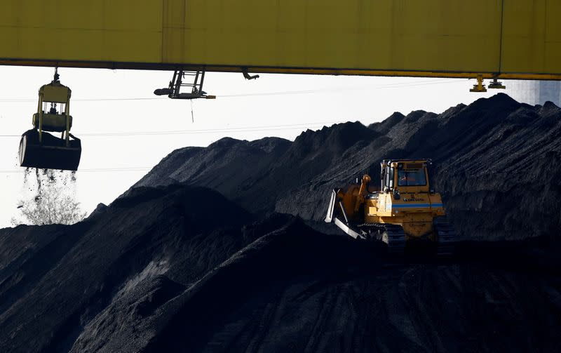 FILE PHOTO: A bulldozer works on a heap of coal at the Zeran Heat Power Plant in Warsaw