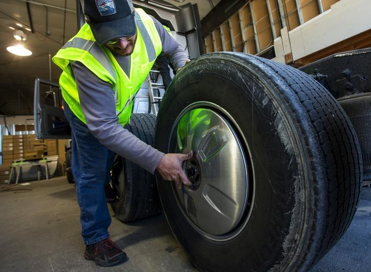 Technician Ryan DiMenza installs an aerodynamic hubcap to a transport truck at Hirschbach Motor Lines in East Dubuque