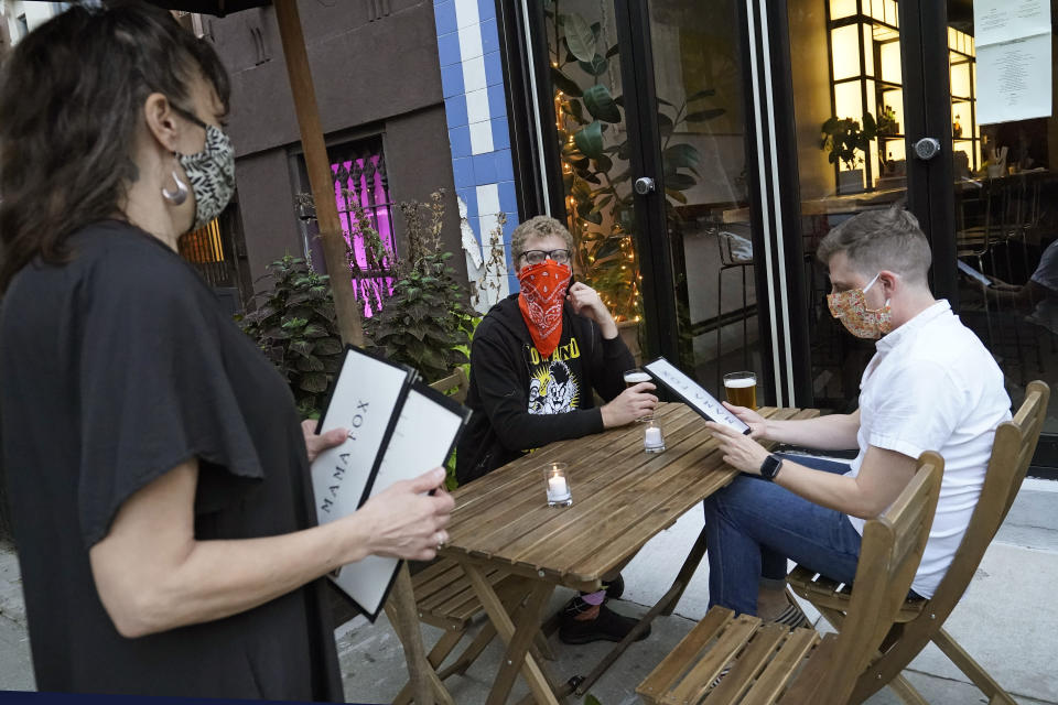 FILE — In this Sept. 29, 2020 file photo, restaurant owner Samantha DiStefano, left, of Mama Fox, prepares to hand menus to patrons dining outside at her Brooklyn establishment, in New York. The coronavirus and the drastic measures put in place by government officials to try to control its spread had a severe toll on many small businesses in the U.S. Restaurants, hair salons, event planners and other businesses that rely on people being in close proximity were particularly hard-hit, as were those tied to tourism. (AP Photo/Kathy Willens, File)