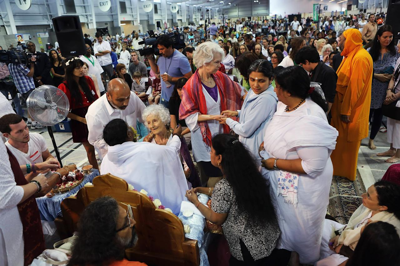 """NEW YORK, NY - JULY 10:  Devotees gather to embrace Mata Amritanandamayi, also known as """"The Hugging Saint"""" on July 10, 2012 in New York City. The Hindu spiritual leader and guru is on a 10-city U.S. tour, where she is expected to bless thousands of people individually at free public gatherings, known as """"darshan"""". Amritanandamayi, 58, from India's southern state of Kerala, is considered a living saint by her followers, who refer to her as """"Amma"""" or mother. She has been giving the public """"darshan"""" gatherings for 35 years, with the aim of bringing good fortune, well-being and grace to her followers through her embrace. Participants are encouraged to donate to her global charitable organizations, known collectively as """"Embracing the World."""" (Photo by John Moore/Getty Images)"""