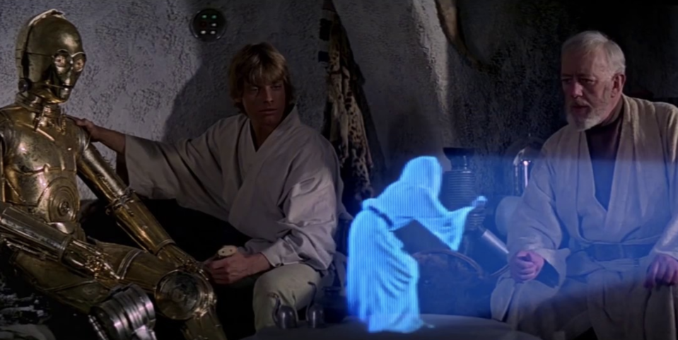 Princess Leia (Carrie Fisher) seeks out hope from Obi-Wan (Alec Guinness), as C-3PO and Luke look on. (Photo: Lucasfilm)