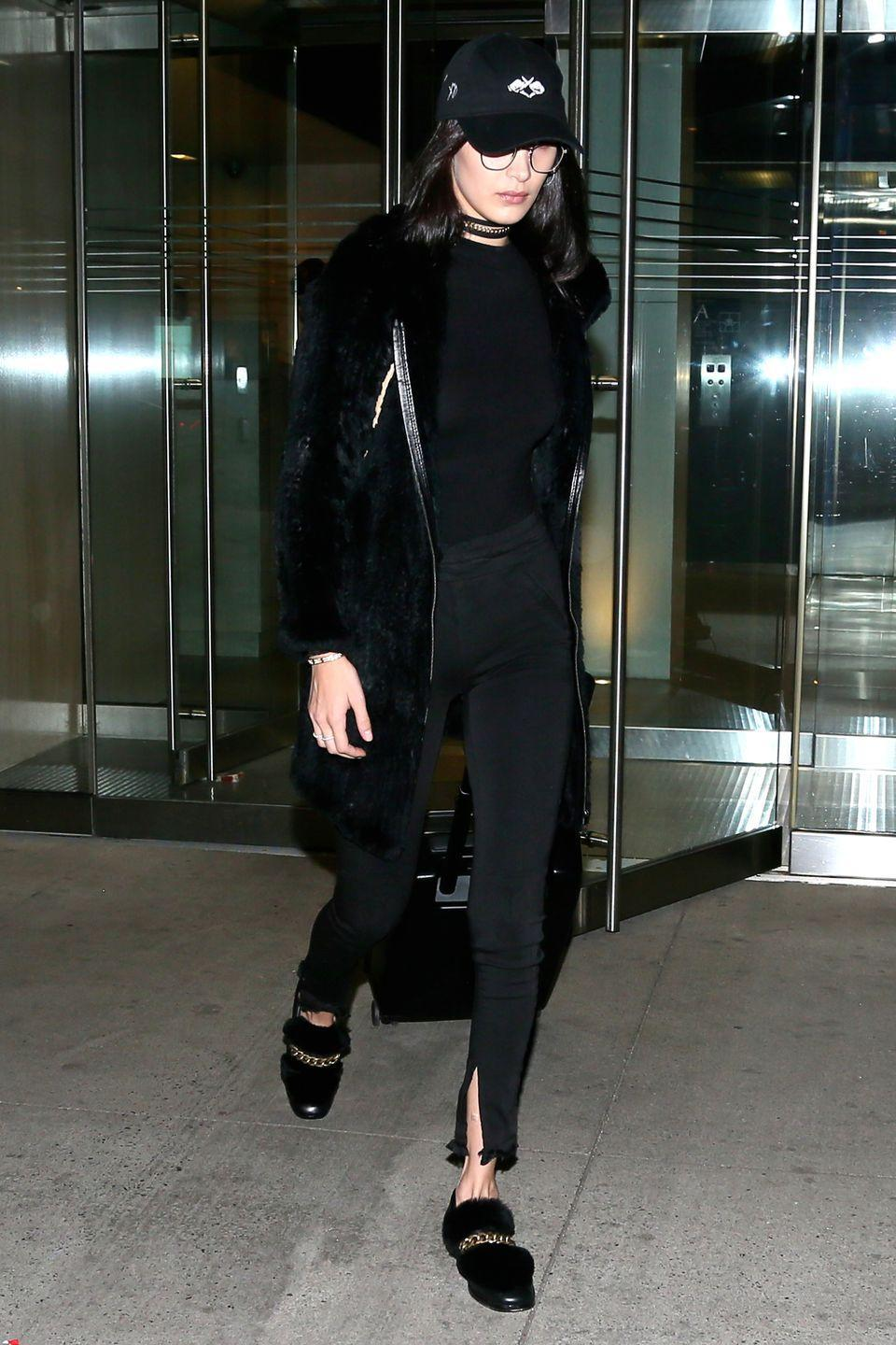 <p>In a black fur coat, string and chainlink choker, a black top, skinny jeans with a slit at the ankle, furry loafers with a chain accent, The Weeknd merch baseball cap and round wire-rimmed glasses while out in NYC.</p>