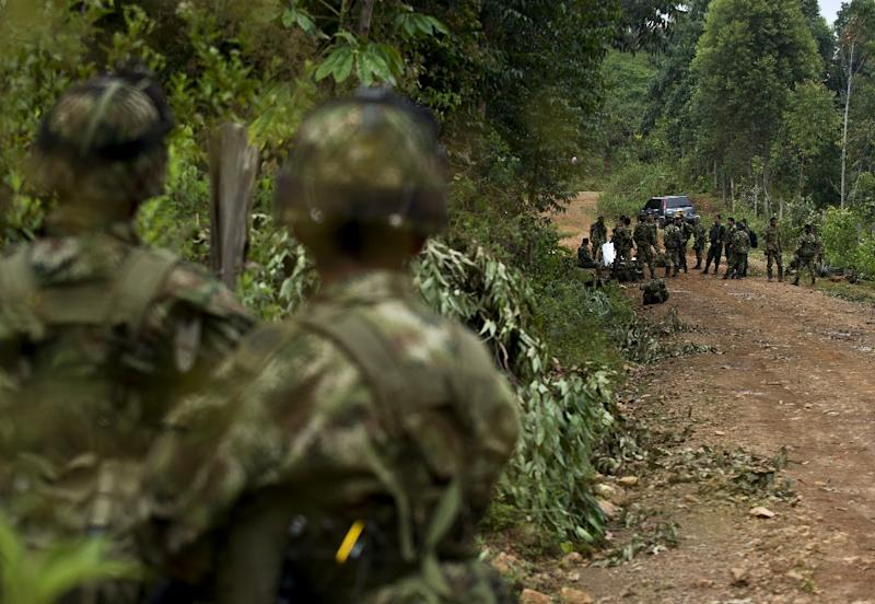 Colombian soldiers stand next to equipment and weapons of ten soldiers killed by FARC guerrillas, in a rural area of Buenos Aires, department of Cauca, on April 15, 2015 (AFP Photo/Luis Robayo)