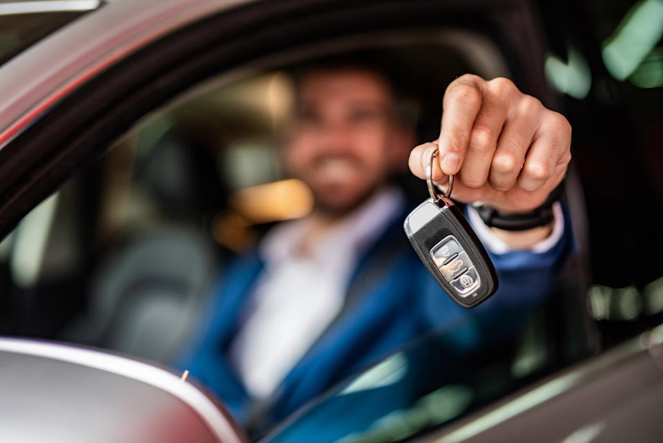 Photo of mid adult man sitting in new car and showing car keys. Focus on foreground.