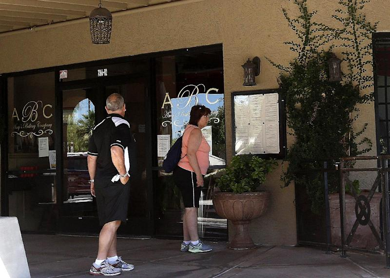 """In this Monday, June 3, 2013 photo, two people approach the front of Amy's Baking Company in Scottsdale, Ariz. The restaurant temporarily closed after their """"Kitchen Nightmares"""" episode aired. The episode of """"Kitchen Nightmares"""" drew more than a million viewers on YouTube, and restaurateur Amy Bouzaglo's vitriolic rants became popular fodder on Twitter and Facebook. Bouzaglo announced she is shopping around her own reality TV show. (AP Photo/Ross D. Franklin)"""