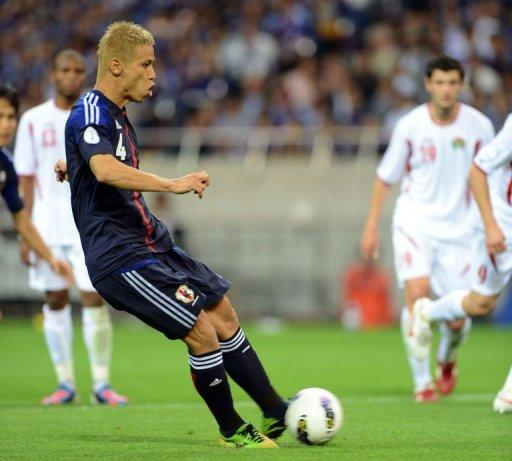 Japan's midfielder Keisuke Honda (C) kicks the ball in a penalty kick