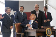 President Donald Trump talks with Sen. Ted Cruz, R-Texas, as he signs a permit for energy development during a visit to the Double Eagle Energy Oil Rig, Wednesday, July 29, 2020, in Midland, Texas. Sen. Ted Cruz, R-Texas, is second from left. (AP Photo/Evan Vucci)