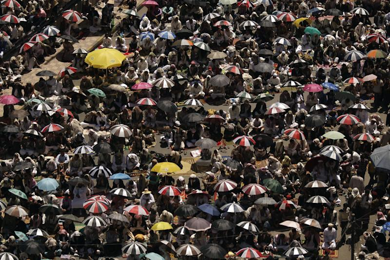 Protestors sit on the ground holding umbrellas as they listen to a sermon during Friday prayers as they gather to demand the trial of Yemen's former President Ali Abdullah Saleh, in Sanaa, Yemen, Friday, March 9, 2012. (AP Photo/Hani Mohammed)