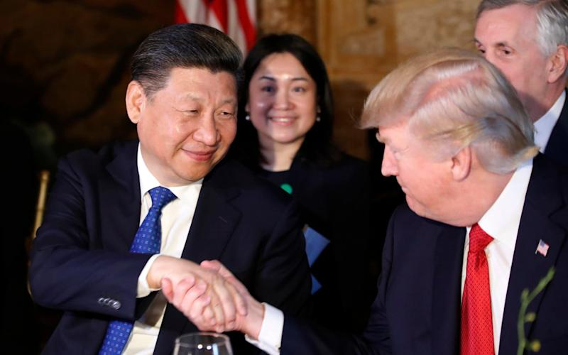 President Donald Trump and Chinese President Xi Jinping shake hands during a dinner at Mar-a-Lago - Credit: AP