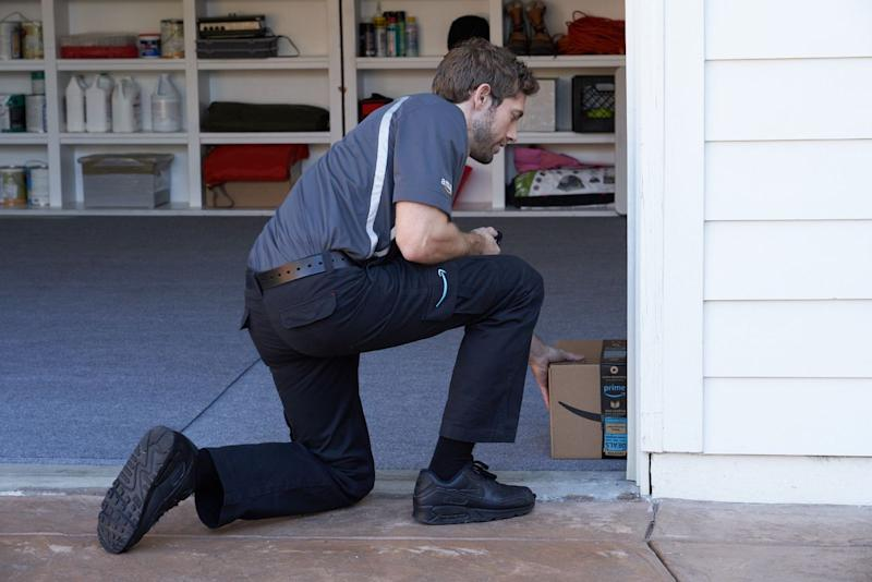 An Amazon driver sliding a package into the corner of a garage.