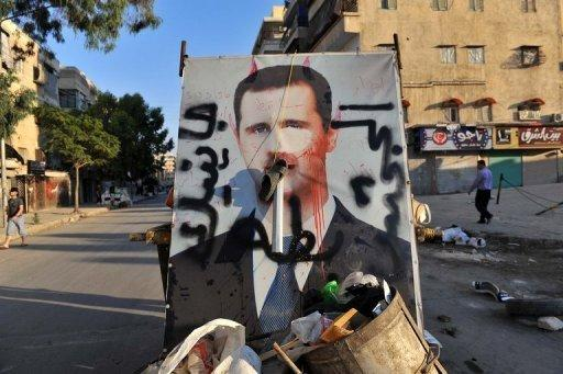 <p>A vandalised poster of Syrian President Bashar al-Assad lies in a trash container in the northern city of Aleppo on July 24. Paris prosecutors opened a preliminary probe Thursday into the alleged involvement of French technology firm Qosmos in supplying Syria's regime with surveillance equipment, judicial sources said.</p>
