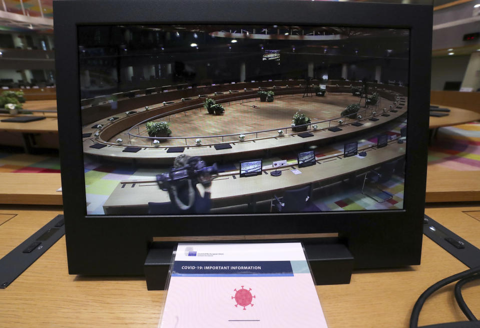 A camera man walks in a meeting room especially adapted to adhere to physical distance guidelines for EU leaders for an upcoming EU summit at the European Council building in Brussels, Thursday, July 16, 2020. On Friday, July 17, 2020, leaders from the 27 European Union nations will meet face-to-face to try to carve up a potential package of 1.85 trillion euros among themselves. Due to coronavirus concerns, Friday's summit will be held in a larger-than-usual meeting room to meet social distancing requirements, the media will be kept to a minimum and there will be no group photo of the leaders. (Yves Herman, Pool Photo via AP)